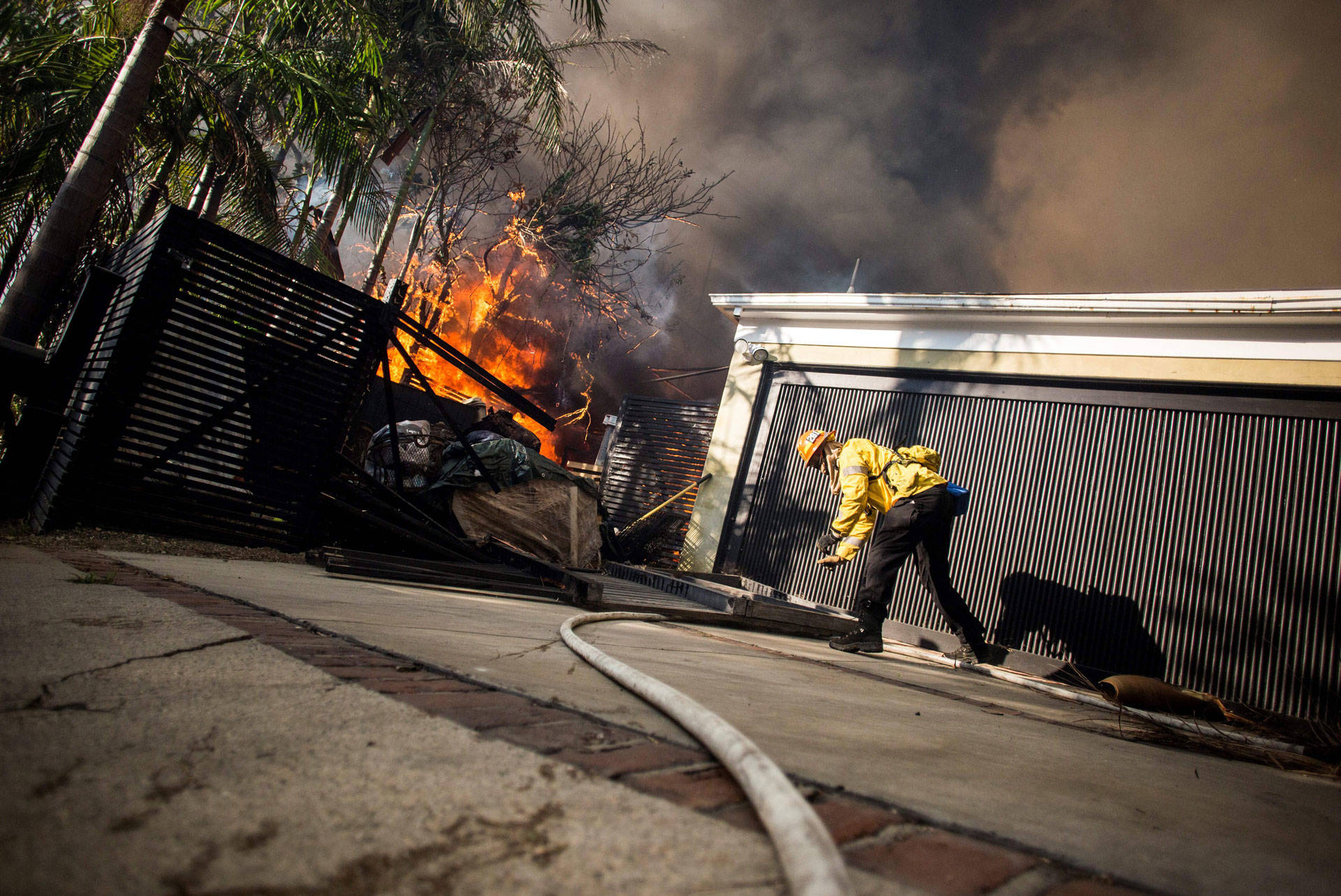 Firefighters work to save burning houses along Linda Flora Drive during the Skirball Fire in Los Angeles on Dec. 6, 2017.