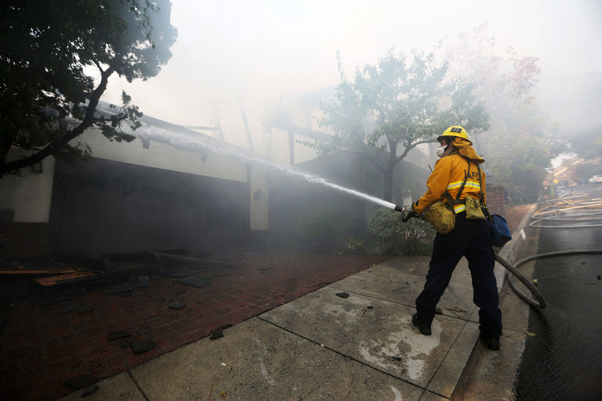 A firefighter sprays water on a burning home in the wealthy Bel-Air neighborhood during the Skirball Fire on Dec. 6, 2017.