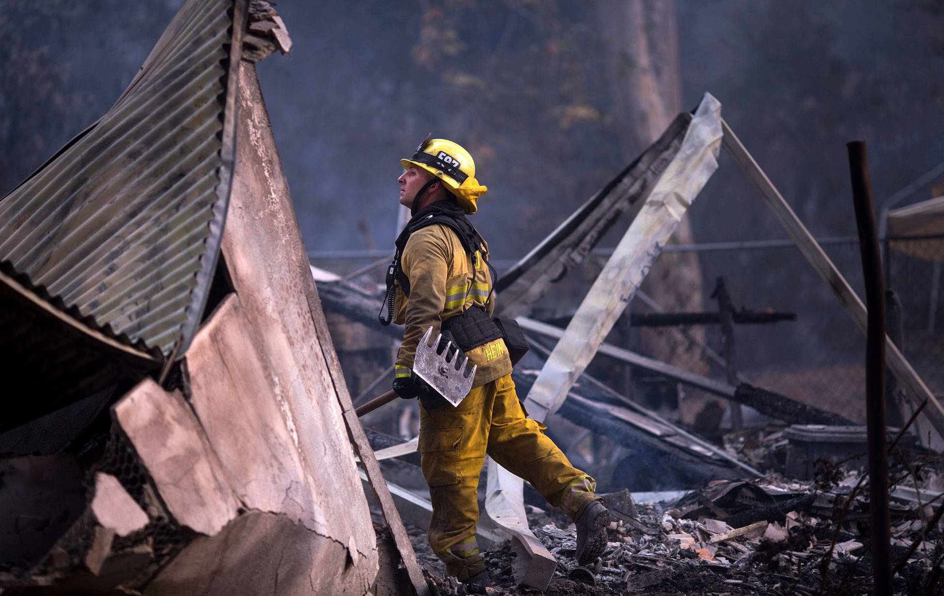 A firefighter looks through the smoldering ruins of a burned house near Casitas Pass Road as the Thomas Fire continued to grow on December 10, 2017 near Carpinteria.