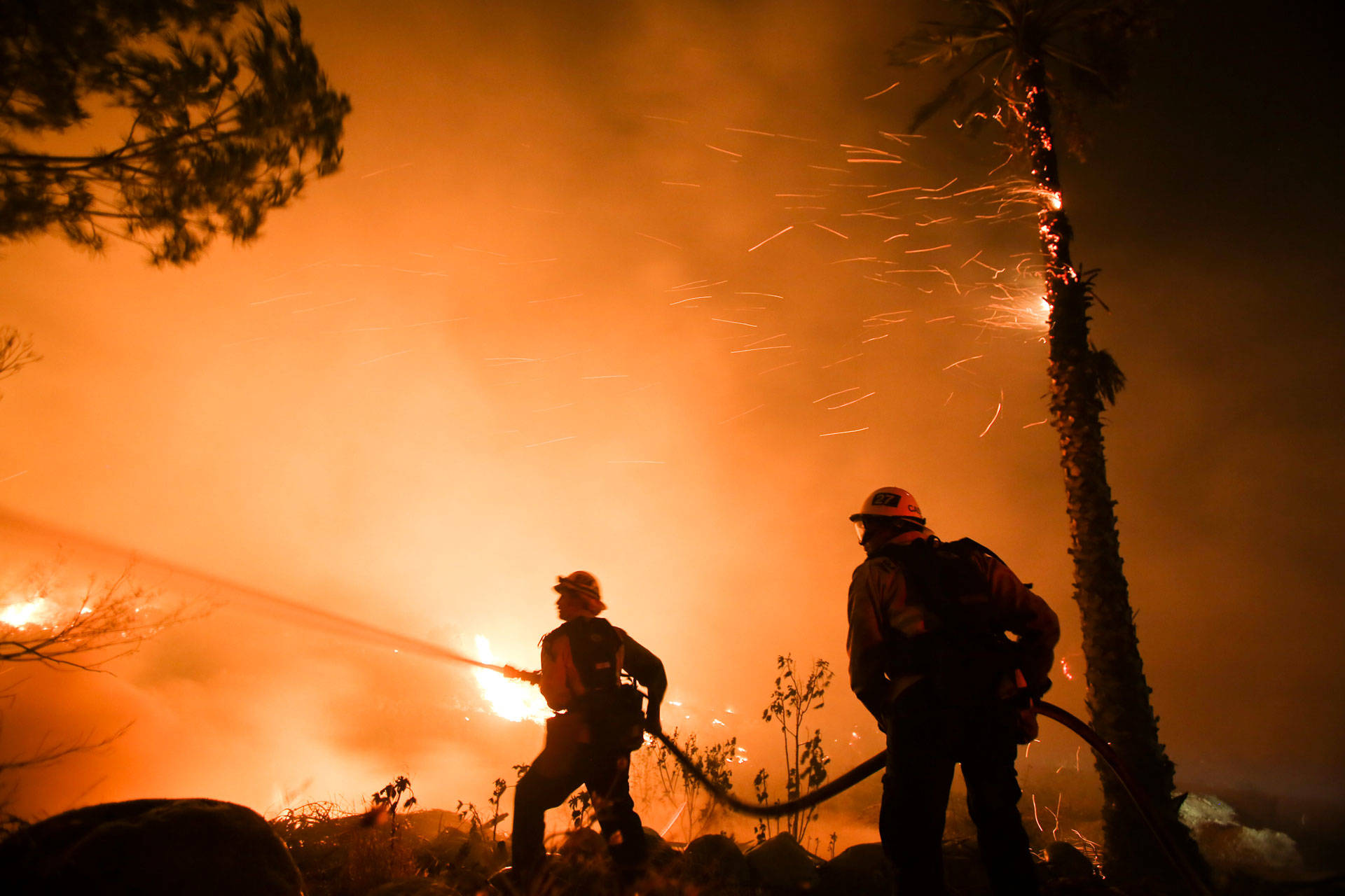 Firefighters battle the Thomas Fire as it burns along a hillside near homes in Santa Paula, northeast of Ventura, on Dec. 5, 2017. RINGO CHIU/AFP/Getty Images