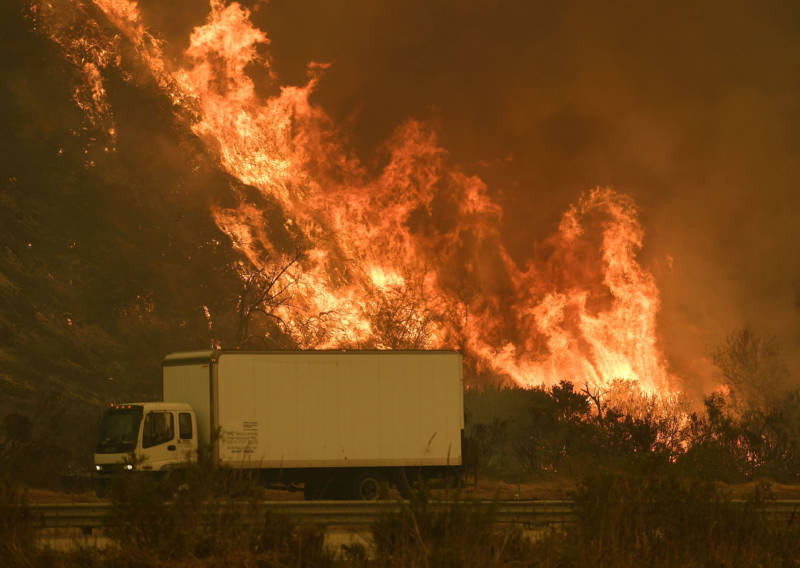Vehicles pass a wall of flame on the 101 freeway as the Thomas Fire reaches the coast near Ventura on Dec. 6, 2017.