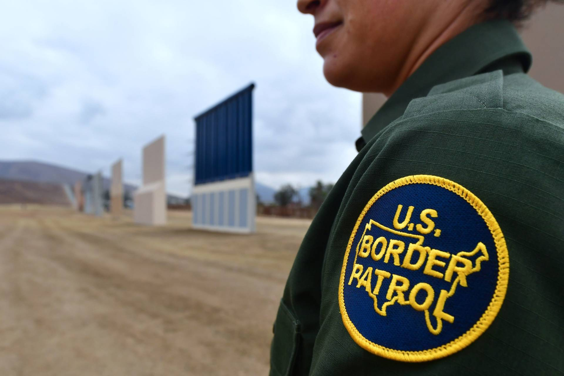 A U.S. Border Patrol officer stands near prototypes of President Trump's proposed border wall in San Diego. Border officers apprehended 310,531 people for being in the country illegally in fiscal 2017, a 25 percent decrease from the year before. Frederic J. Brown/AFP/Getty Images