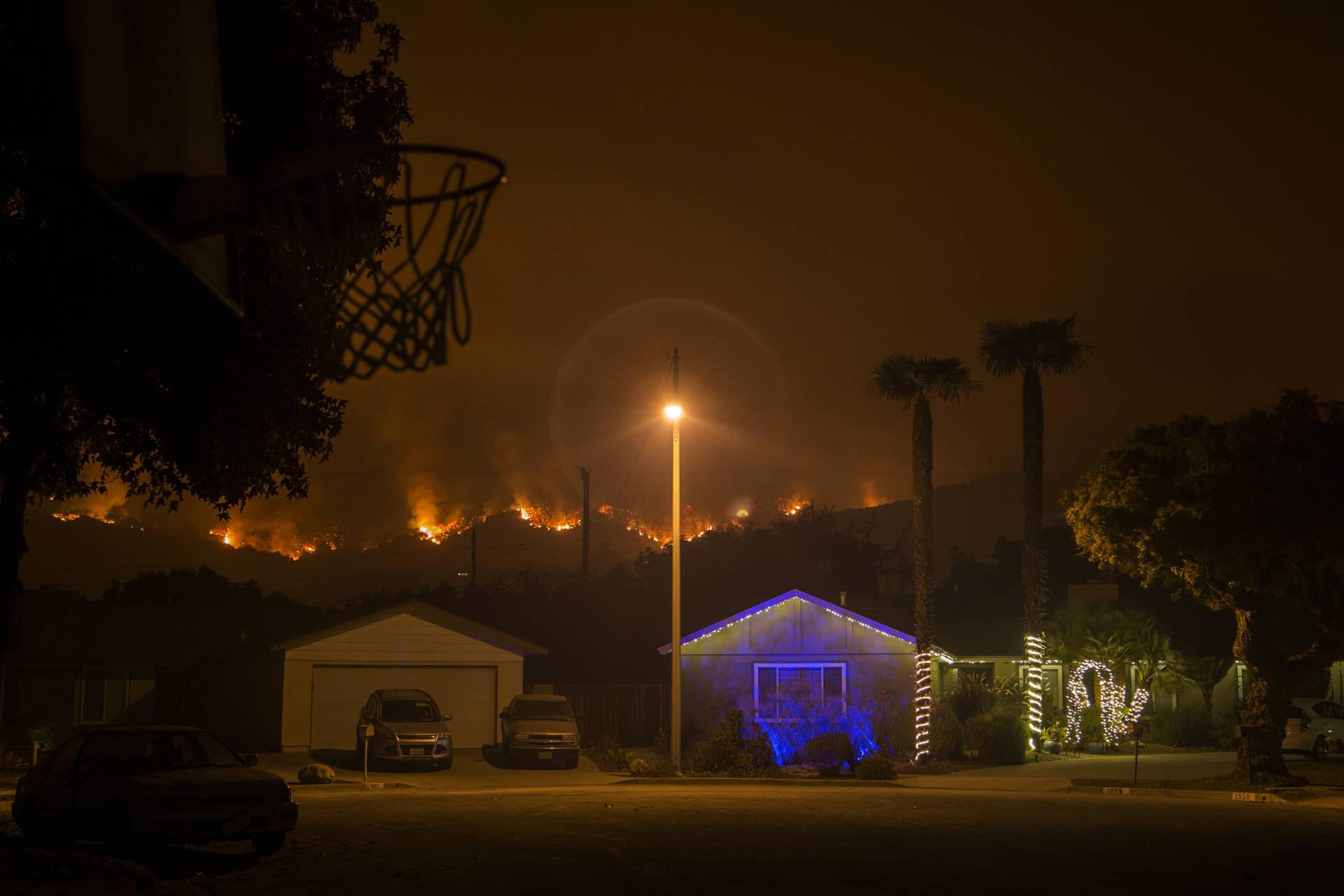 Christmas decorations illuminate a house as the growing Thomas Fire advances toward Santa Barbara County seaside communities. David McNew/Getty Images