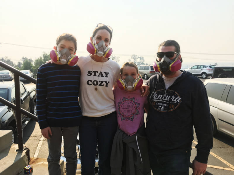 Nancy and Jay Blomquist stand outside the Local Assistance Center in Ventura, with their twins, Alexander and Olivia. The family wears masks to protect themselves from the ash and smoke in the air from the Thomas Fire.