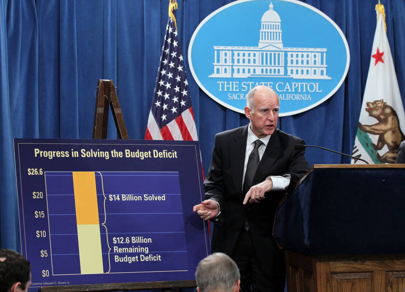 Gov. Brown points to a chart showing dollar amounts in the billions that were cut from the state budget following a bill signing on March 24, 2011.