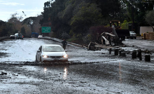 A vehicle drives across the flooded US 101 freeway in Montecito on January 9, 2018.