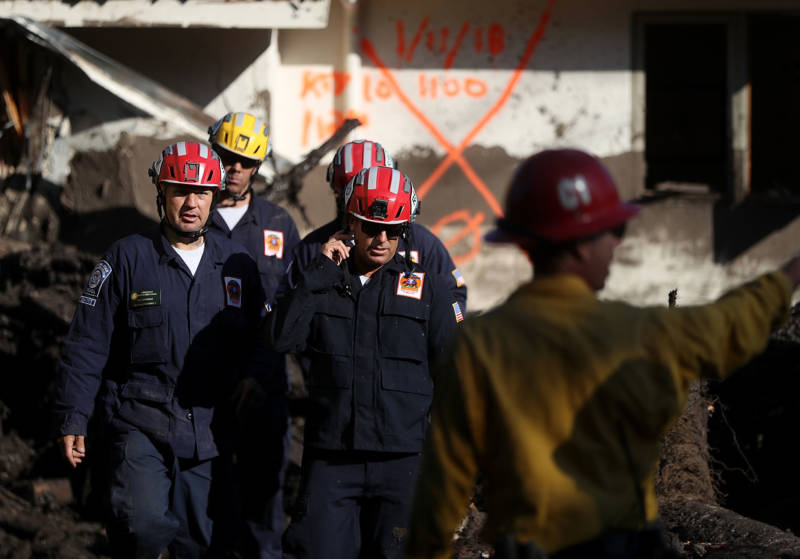 Los Angeles County firefighters prepare to investigate a home after a cadaver dog alerted on a pile of debris from a mudslide on January 11, 2018 in Montecito.