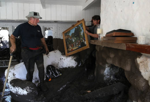 David Drenic (L) and Robert Drenic (R) look for salvageable items in a the home of a family member that was destroyed by a mudslide on January 11, 2018 in Montecito, California.