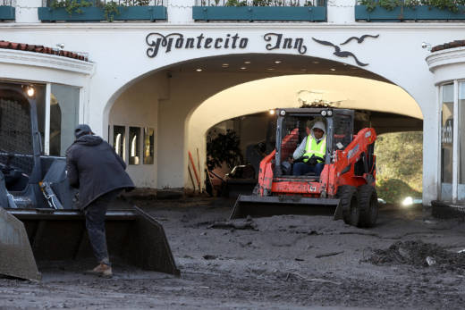 Workers clear mud from the parking garage at the Montecito Inn following a mudslide on January 12, 2018 in Montecito, California.