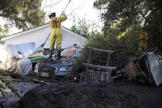 A Cal Fire firefighter looks through a car next to a home that was destroyed by a mudslide on January 12, 2018 in Montecito, California. At least 18 people have died and hundreds of homes have been destroyed or damaged after massive mudslides crashed through Montecito, California early Tuesday morning.