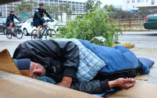 A homeless man sleeps at his encampment in downtown Los Angeles.