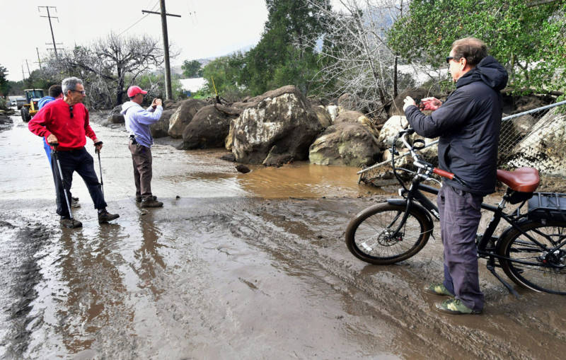 Residents have a look at boulders which were carried down nearby hillsides by flooding in Carpinteria on January 9, 2018.