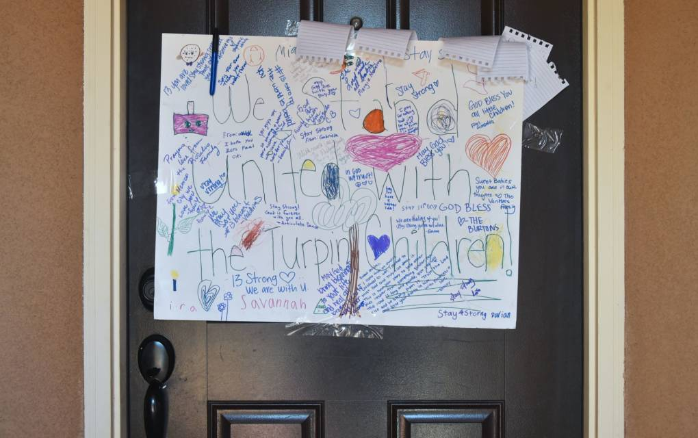 Personal handwritten notes are seen on a piece of paper hanging on the front door of the Turpin family's home in Perris, California on January 24, 2018. Parents David and Louise Turpin were arrested on January 14 for allegedly torturing and starving their 13 children.