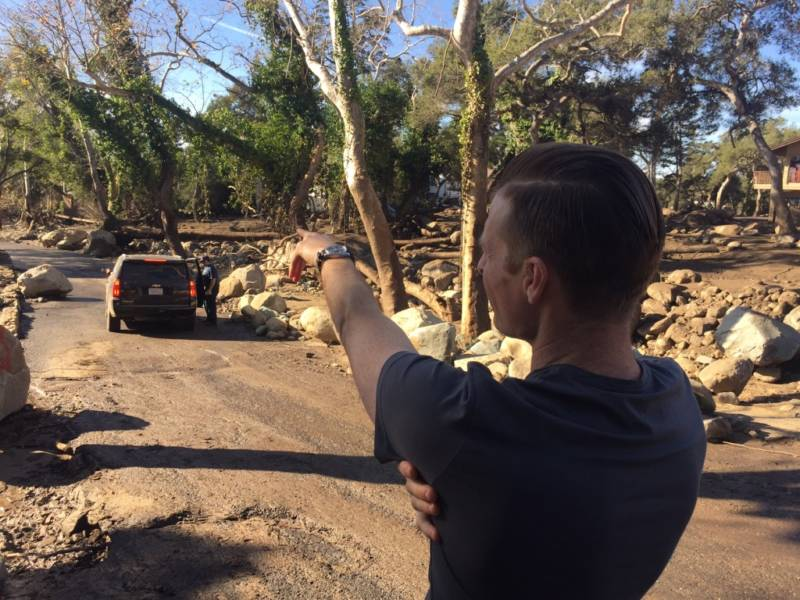 Geoff Gray points down the road to a guest cottage where he, his wife and his daughter narrowly escaped the deadly mud and debris flows that followed the first major storm of the season.