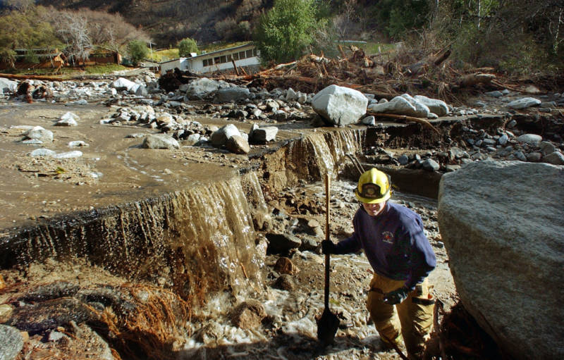 Rialto Firefighter Dave Denman searches for victims after a mudslide December 26, 2003 in Waterman Canyon, California. The mudslide which killed at least four, and left 12 missing was caused by heavy rains.