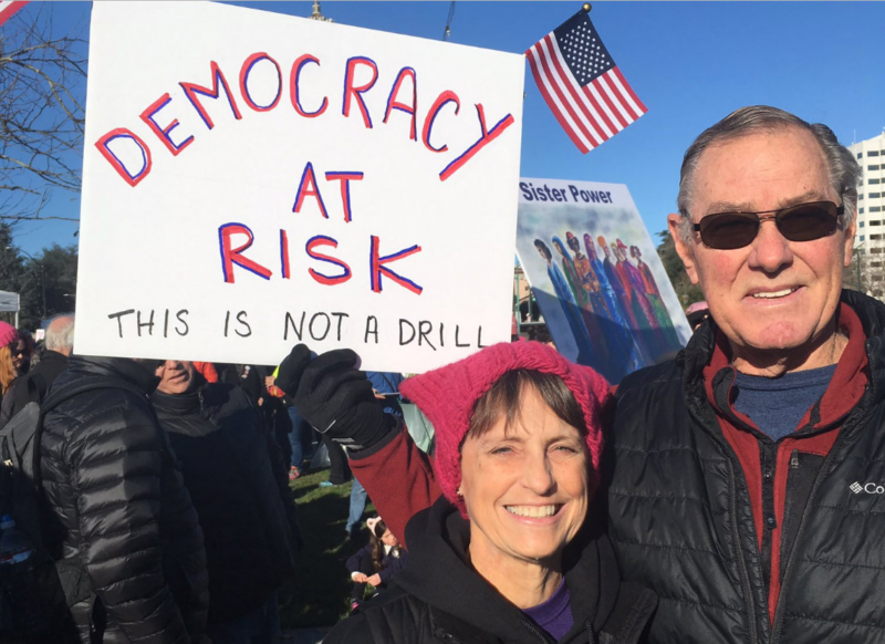 "Kay Bargmann, of Brentwood, is at the Oakland Women's March with her husband. She says President Trump is ""undermining the free press, undermining the justice system, and doing his best to undermine the investigations."""