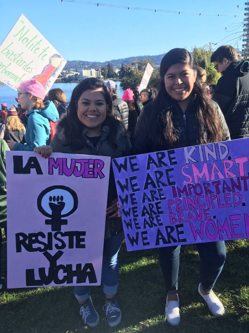 "Mari Ana Flores (right) is at the Oakland Woman's March as a student of a St. Mary's College class called ""Protest, Parade and Pop Music."" She says the focus of class last week was Black Lives Matter, next week is Chicano rights, and this week is women."