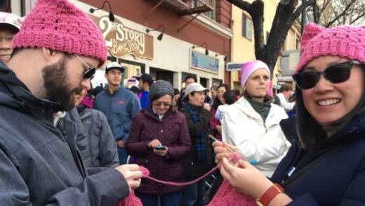 """Patricia Leung and her husband Jonathan Evans of Santa Clara crochet pussy hats at the Women's March in 2017. """"I'm actually behind,"""" Leung says. """"I have three more people who've asked me for hats. One person in the crowd asked and I ripped it off my head and gave it to him. I can't keep them in stock!"""""""