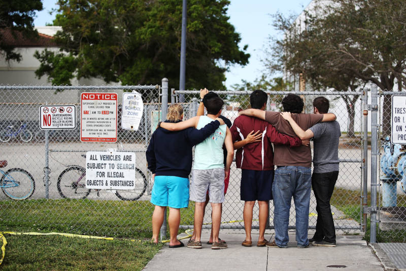 People look on at the Marjory Stoneman Douglas High School on February 18, 2018 in Parkland, Florida. Police arrested 19 year old former student Nikolas Cruz for the mass shooting that killed 17 people on February 14.
