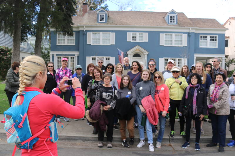 "The ""Lady Bird"" walking tour group poses in front of the stately blue home from the film."