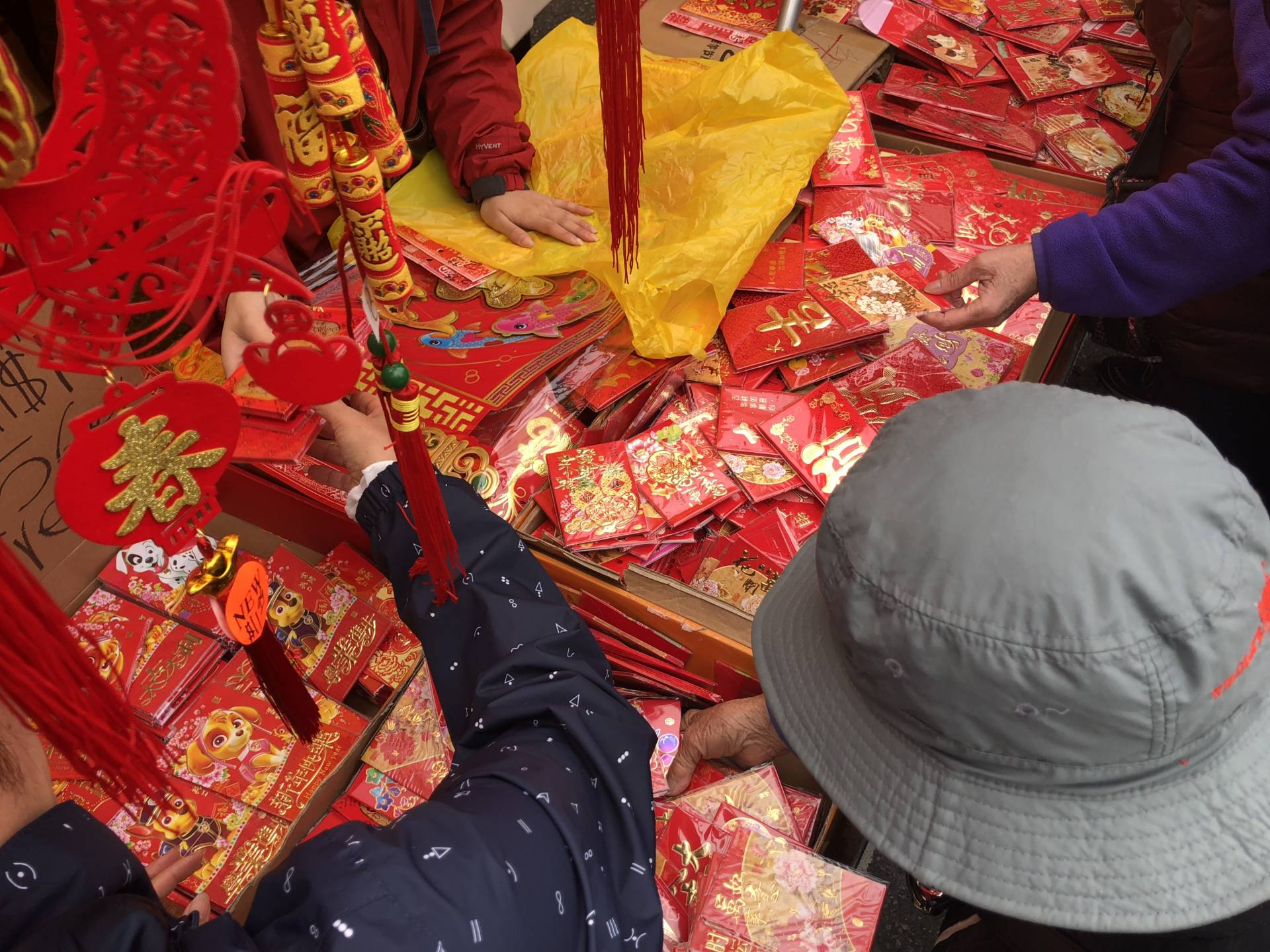 Elderly ladies pick over red envelopes at the Chinese New Year Flower Market Fair. The market is held before Chinese New Year proper in order for people to buy flowers, fruit, candy and plants before the new lunar year.