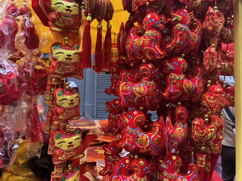 Merchandise featured motifs for the Lunar New Year of the Dog. Stalls selling decorations, plants and more lined a red and gold bedecked street in Chinatown.
