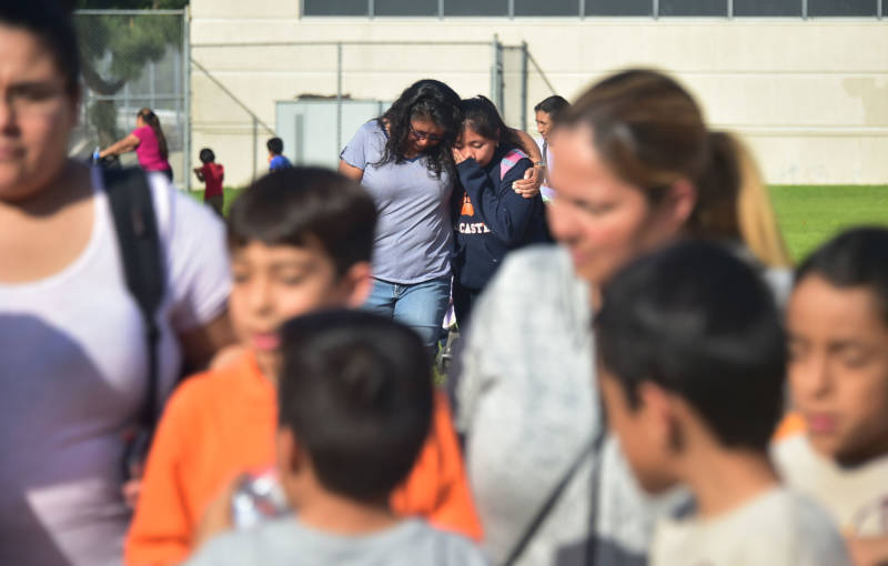 A mother and daughter grieve as parents pick up their children following a shooting at Salvador Castro Middle School in Los Angeles on February 1, 2018.