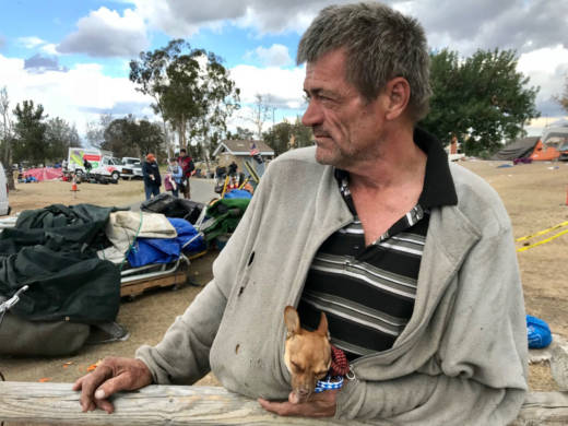 Fritz Reichenbach waits along the Santa Ana River to board a van for a motel in Buena Park where he'll stay for 30 days.