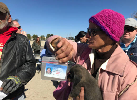 Serena Welch holds up an Orange County-issued ID card as she waits in line for a motel voucher on Feb. 20, 2018.