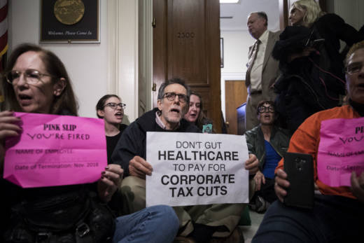 Activists stage a sit-in to protest the GOP tax reform bill outside the office of Rep. Dana Rohrabacher (R-CA) on December 5, 2017. Voters in Rohrabacher's coastal Orange County district now say they want someone new in office, by 51 to 41 percent.