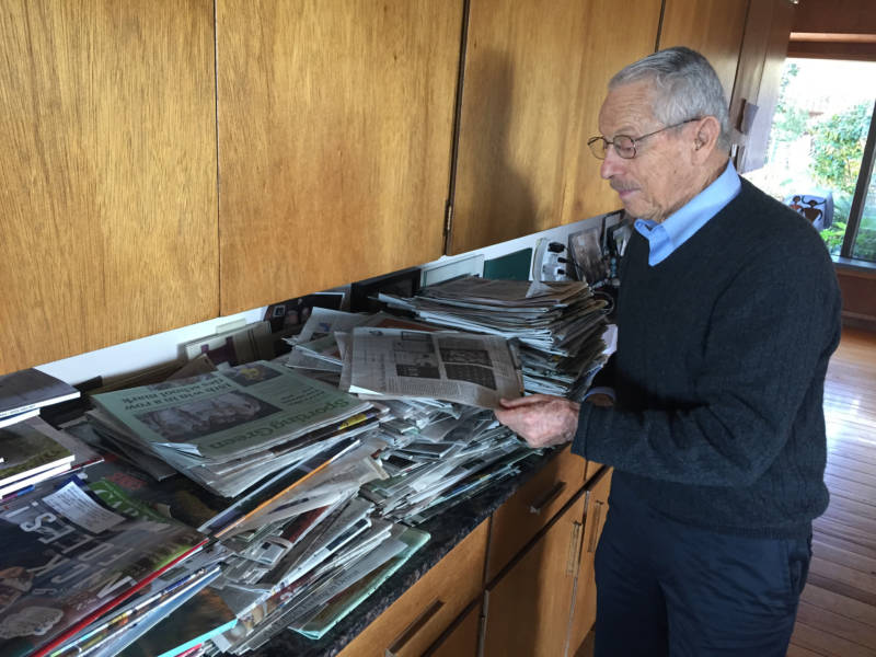 Art Spander looks at a newspaper in his East Bay home. He's covered sports in the Bay Area for more than 50 years.