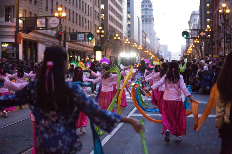 Ribbon dancers prance down Market Street in synchronization, entertaining a crowd of thousands of spectators.