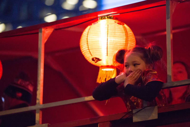 A young girl observes the crowd below on a float decorated with illuminated red and gold lanterns. In traditional Chinese culture, red and gold signify luck and prosperity for the upcoming year.