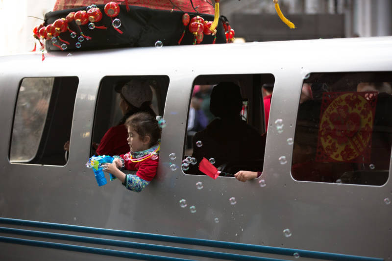 A float resembling a BART train car rolls down Market leaving a trail of bubbles to celebrate the Year of the Dog.