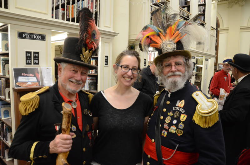 Jennifer Jacobs stands with Rick Saber (L) and Joseph Amster (R), two official Emperor Norton impersonators at Emperor Norton's 200th birthday party at the Mechanics' Institute in San Francisco on Feb. 7, 2018.