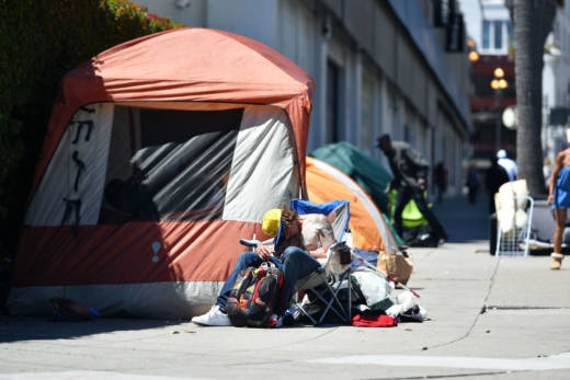 A homeless man sleeps in front of his tent along Van Ness Avenue in San Francisco.