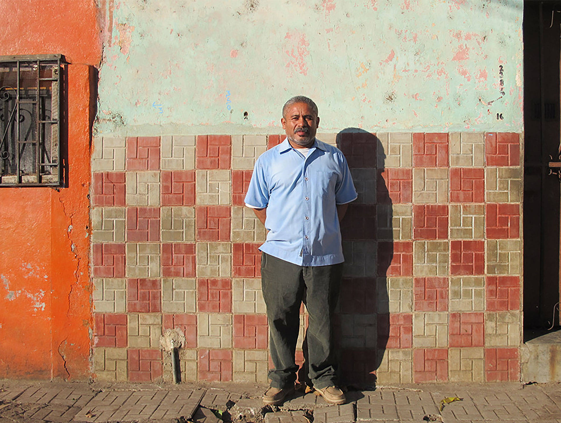 Juan Vicente in front of his grandparents' old home in Santa Ana, El Salvador. Vicente fled El Salvador's civil war in 1981 and sought refuge with his family in Bell Gardens, California. He was deported to El Salvador more than three decades later.  Levi Bridges/KQED