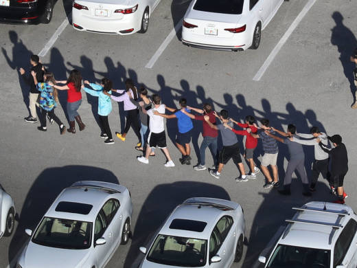 People are brought out of the Marjory Stoneman Douglas High School after a shooting at the school that killed at least 17 people on Wednesday in Parkland, Fla.