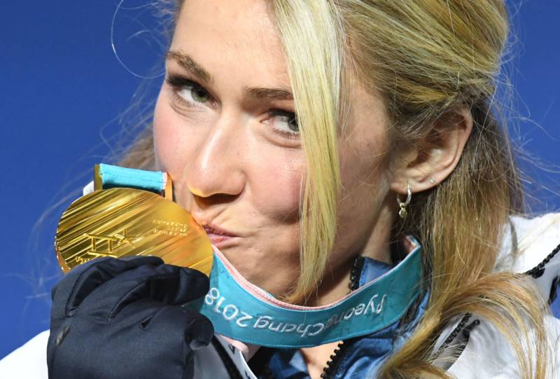 Team USA's Mikaela Shiffrin kisses her gold medal on the podium during the medal ceremony for the women's alpine skiing giant slalom.