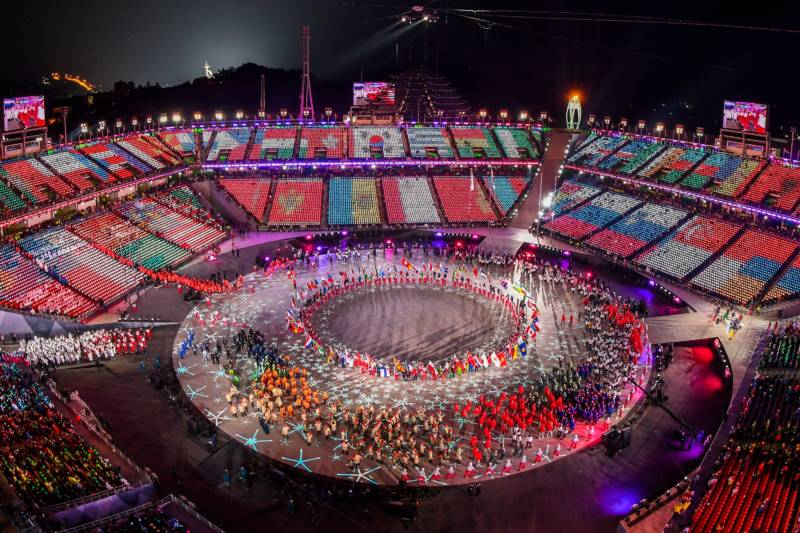 Flags are projected on the stands as athletes enter the stadium.