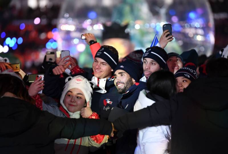 France's biathlon champion Martin Fourcade (center), who won three gold medals in Pyeongchang, poses for a selfie with athletes and volunteers during the closing ceremony.