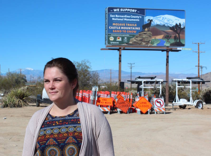 Breanne Dusastre of the 29 Palms Inn stands in front of a billboard she and other business leaders had installed along Highway 62 in Twentynine Palms, California, showing their support for national monuments and other protected lands.