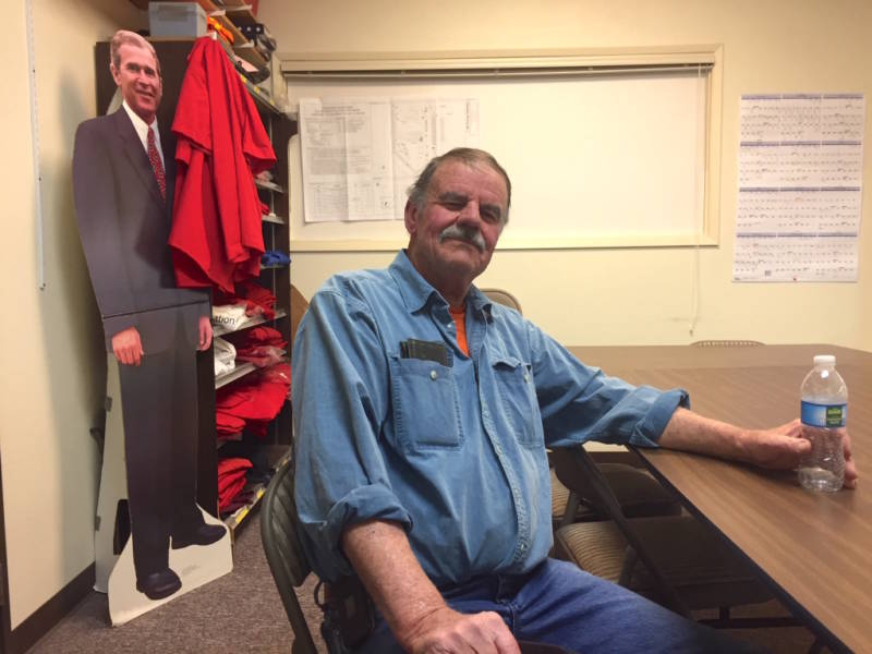 Chuck Bell with the Lucerne Valley Economic Development Association sits in a conference room above the town's only grocery store, where the owners still display a cardboard cutout of George W. Bush. Bell supports expanding mining in the California desert.