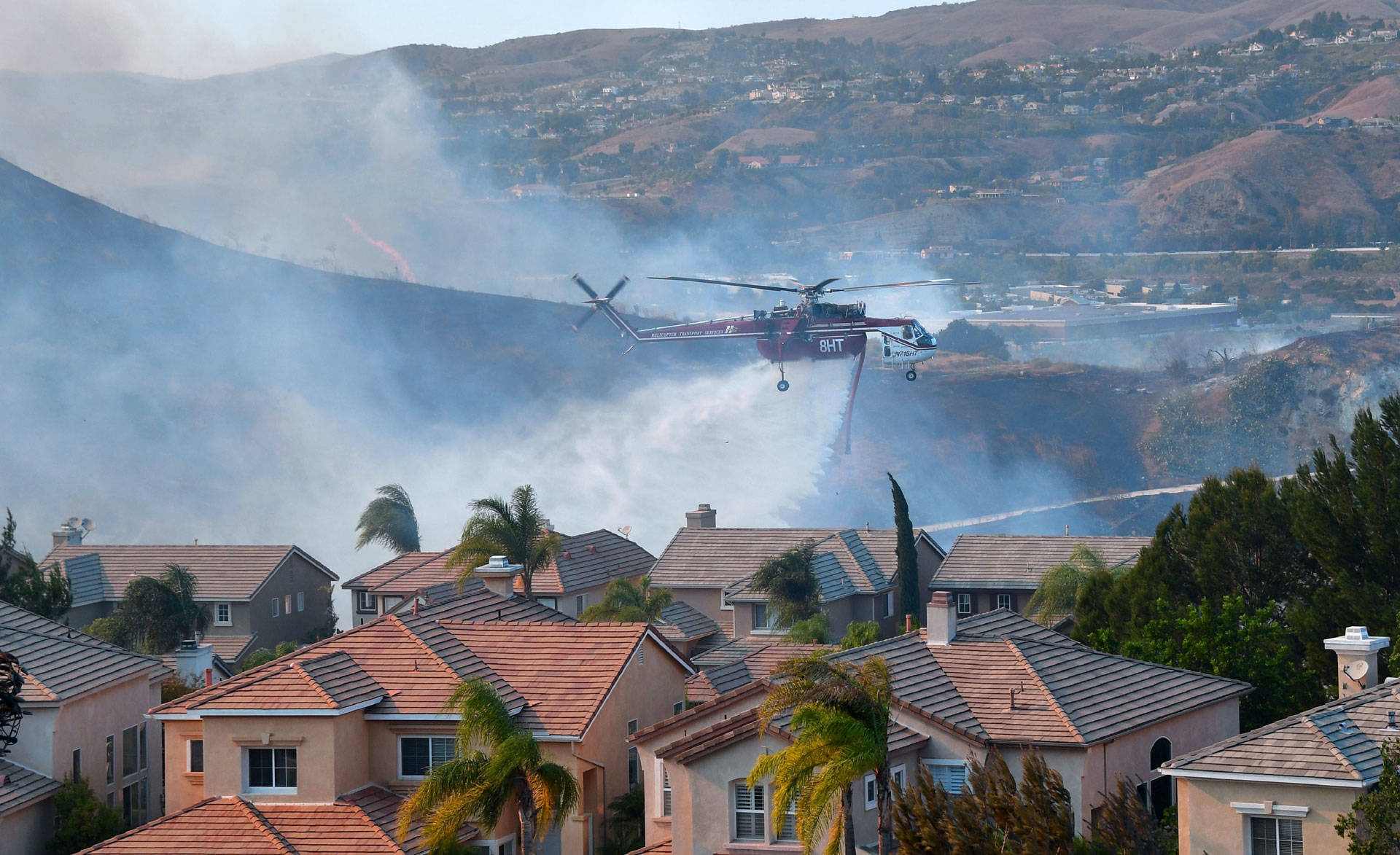 A helicopter drops water near homes in the Anaheim Hills neighborhood on Oct. 9, 2017. Orange County experienced rapid growth in housing construction in fire-prone areas between 1990 and 2010. FREDERIC J. BROWN/AFP/Getty Images