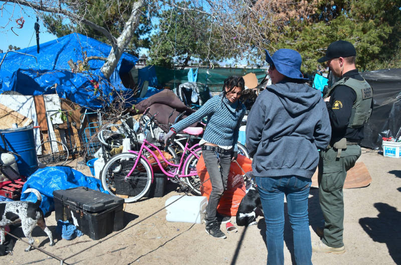 An officer from the Sheriff's Department and a social worker speak with a woman at the homeless encampment beside the Santa Ana River in Anaheim on February 20, 2018.