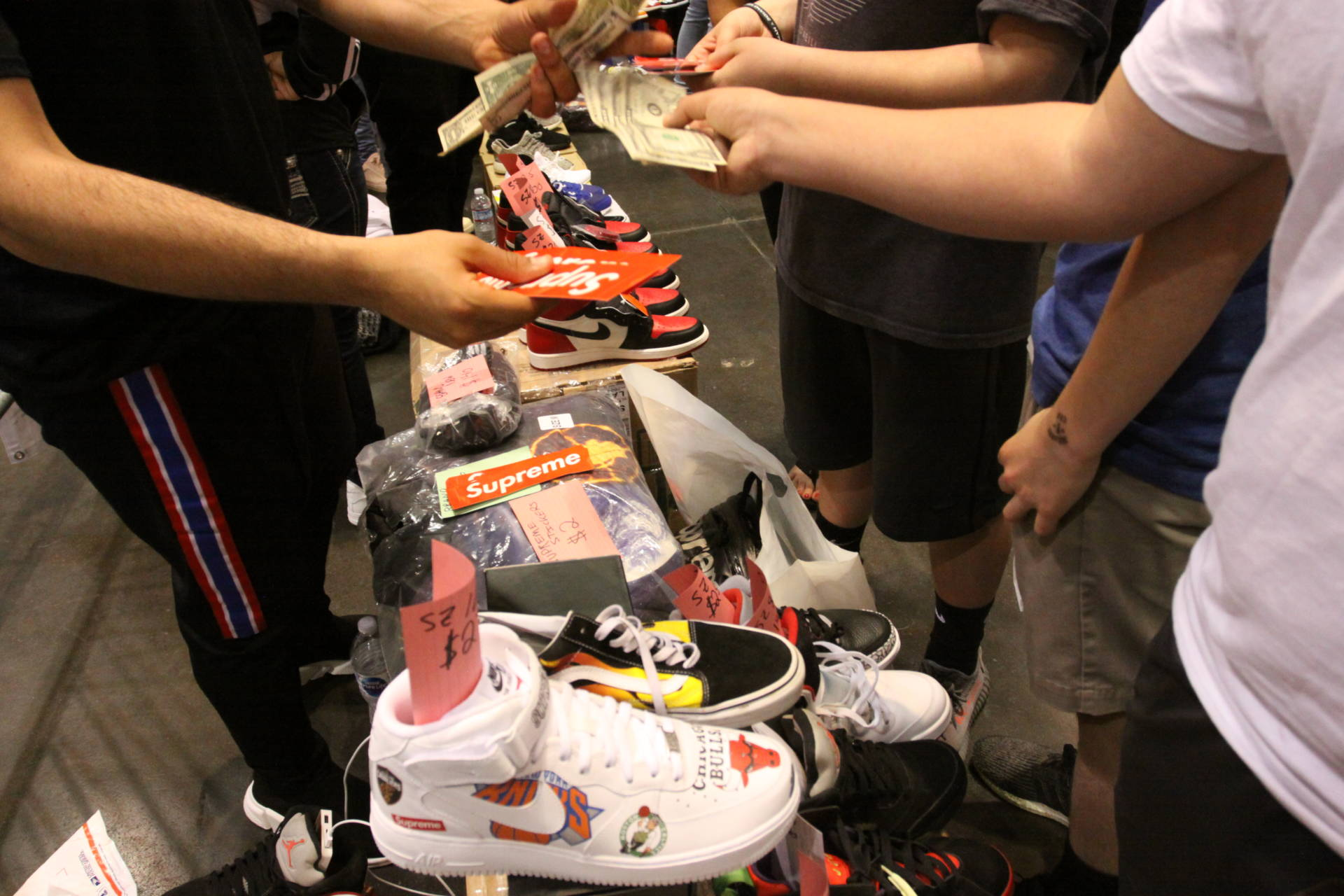Buyers and sellers exchange goods for cash on the Sneaker Con Trading Pit floor.