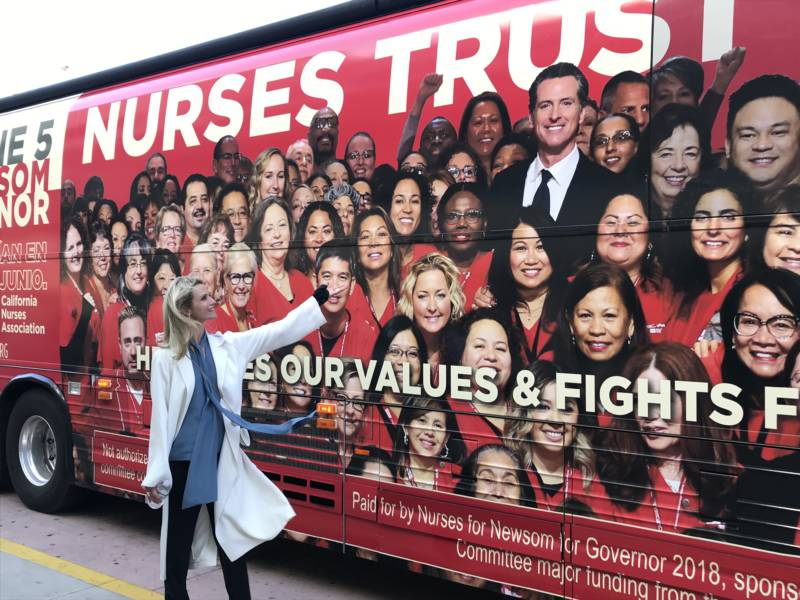 Jennifer Siebel Newsom, wife of Lt. Gov. Gavin Newsom, stands beside a bus from the nurses' union supporting him for governor.