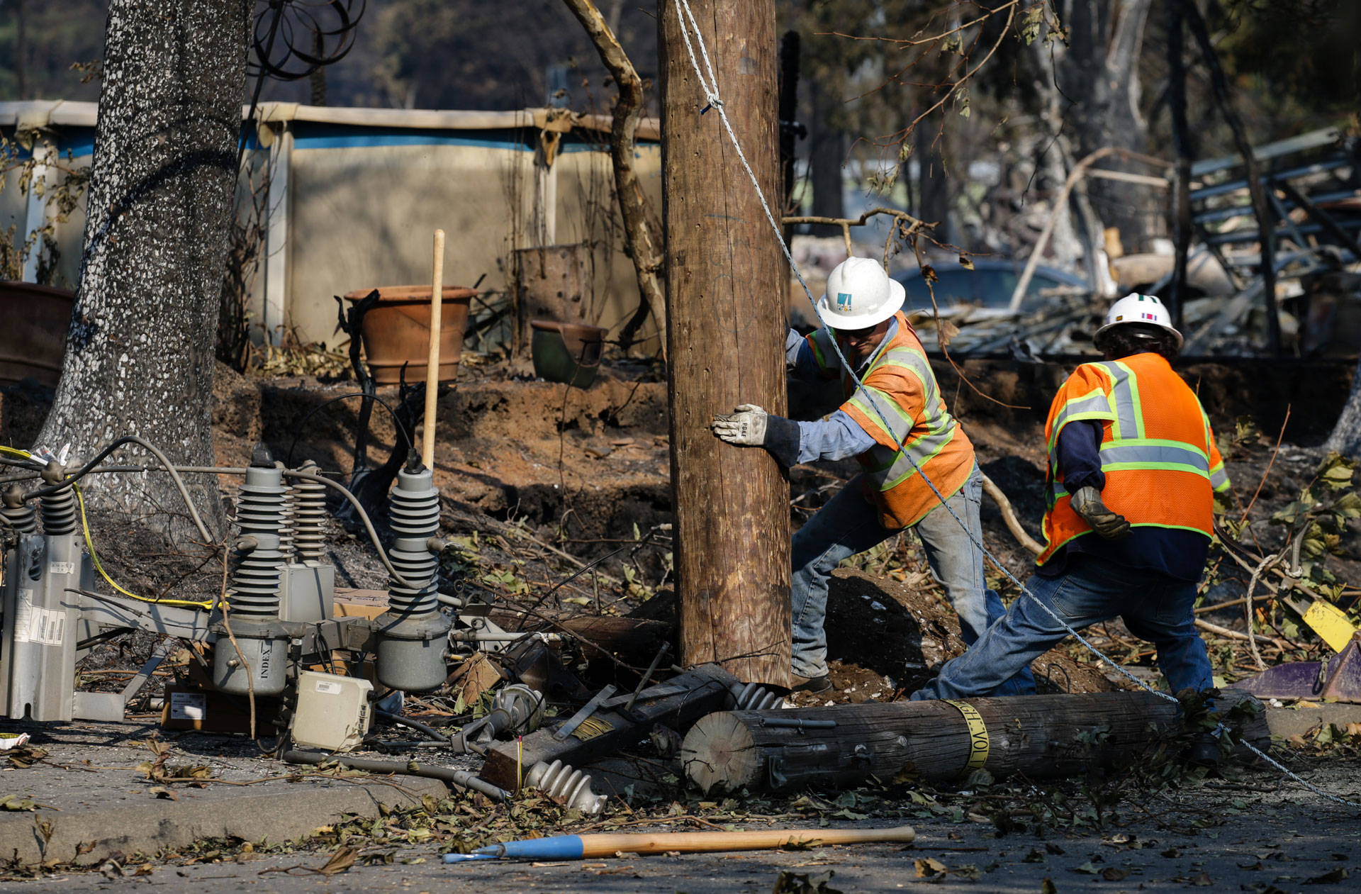 PG&E workers repair power lines in Santa Rosa's devastated Coffey Park neighborhood following the Tubbs Fire in October 2017. Elijah Nouvelage/Getty Images