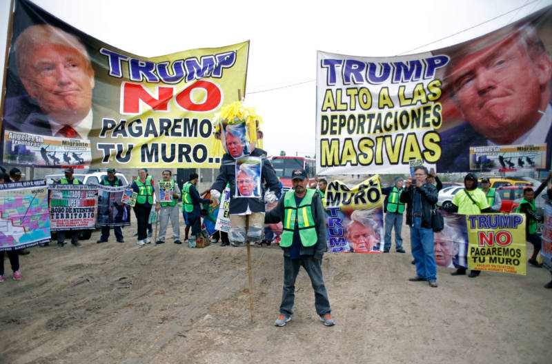 Demonstrators protest against President Donald Trump's migration policies on the Mexican side of the border in Tijuana on March 13, 2018, as President Trump toured border wall prototypes.