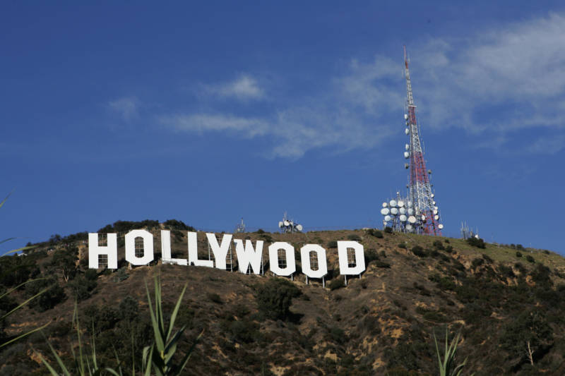 Color photo of the Hollywood sign with blue sky above